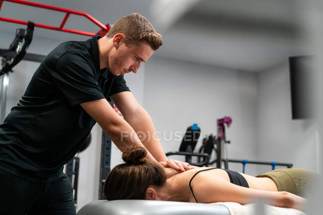 Fisioterapeuta masculino sin afeitar masajeando la espalda de una mujer anónima en la cama durante el procedimiento médico en el hospital - foto de stock
