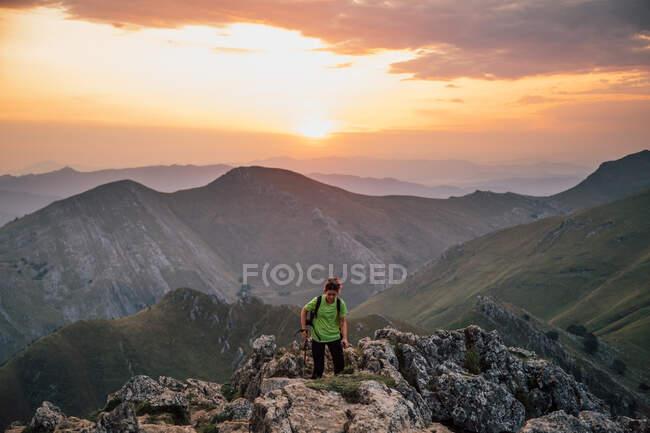 Escursionista femminile distante sull'alta vetta rocciosa della montagna contro la maestosa catena sotto il cielo nuvoloso al tramonto — Foto stock