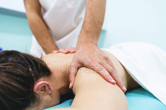 Неупізнаваний чоловічий фізіотерапевт масажує на спині нерозпізнаної жінки на ліжку в лікарні. — стокове фото