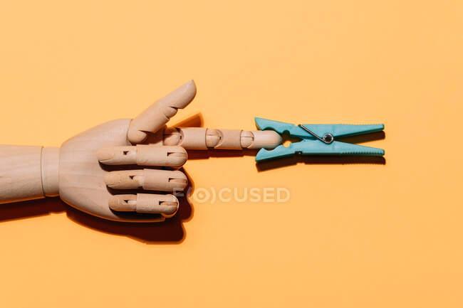 Desde arriba de la mano de madera artificial con pinza de tela azul en el dedo colocado sobre fondo naranja - foto de stock