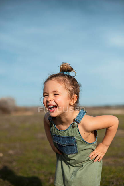 Delighted adorable little girl in overalls standing with hands on waist in meadow and looking away — стокове фото