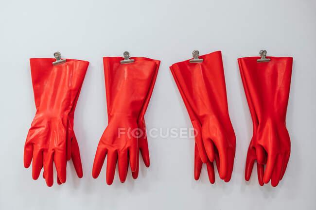 Композиція червоних гумових рукавичок, що висять на шкіряних шпильках на білому фоні у студії — стокове фото