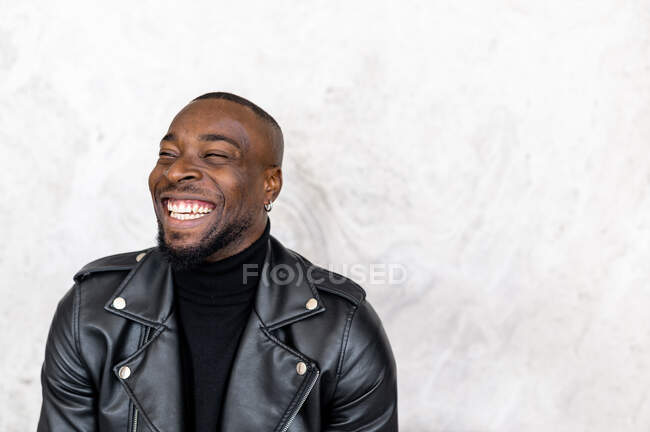 Delighted African American male in stylish leather jacket looking away and smiling happily — стокове фото