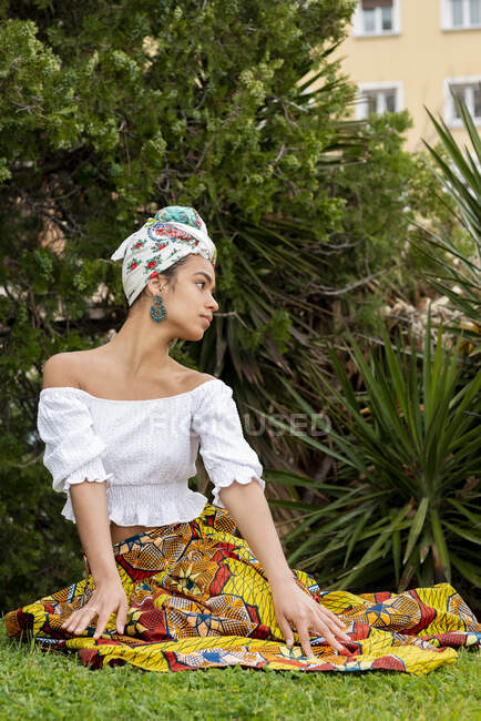 Cheerful young ethnic female in ornamental African skirt against palm plants on meadow — Stock Photo
