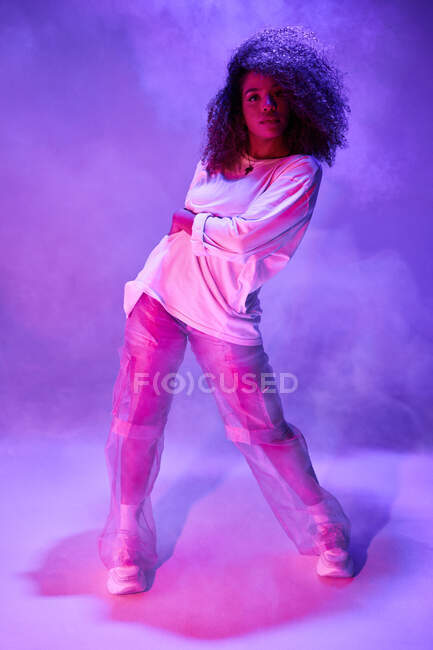 Full length fit young African American female dancer in loose informal wear looking at camera while dancing in dark studio in neon lights — Stock Photo