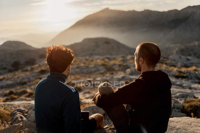 Arrière vue anonyme hommes amis en tenue décontractée reposant sur le sommet des montagnes rocheuses et admirant coucher de soleil pittoresque sur les hauts plateaux rugueux à Séville Espagne — Photo de stock