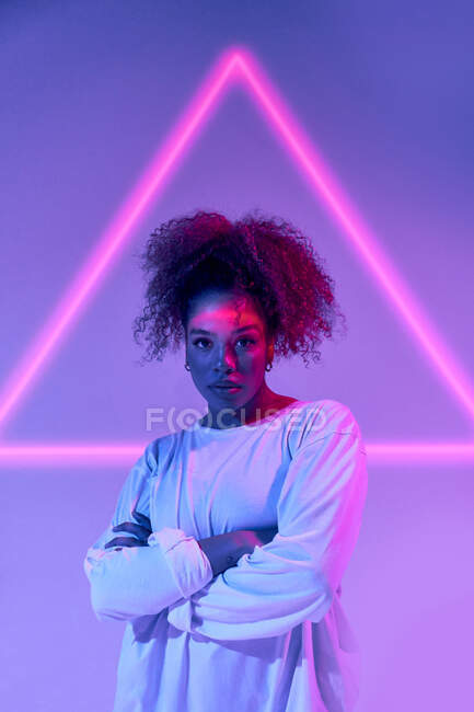 Confident young African American female with curly hair standing with arms folded and looking at camera in neon lights — Stock Photo