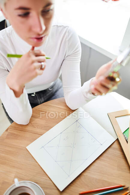 From above female astrologist with cellphone drawing lines in paper album at table in light house — Stock Photo