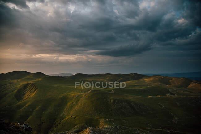Vista pitoresca da cordilheira com grama verde sob nuvens sombrias nubladas no céu à noite — Fotografia de Stock