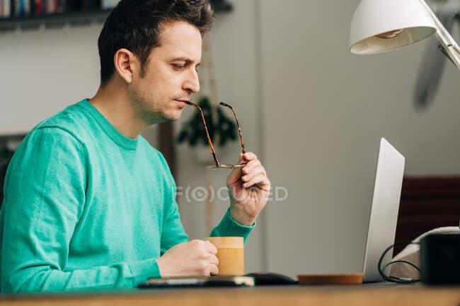 Бічний вид на чоловіків на відстані з кухлем гарячого напою проти нетбука вдома. — стокове фото