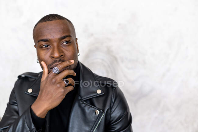 Serious adult African American male wearing black leather jacket touching chin and looking away pensively while standing against white wall — Stock Photo