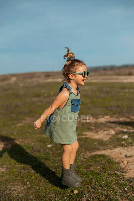 Вид сбоку довольная маленькая девочка в комбинезоне и солнцезащитных очках, прыгающая с распростертыми руками выше головы и наслаждающаяся летом в солнечный день в сельской местности — стоковое фото