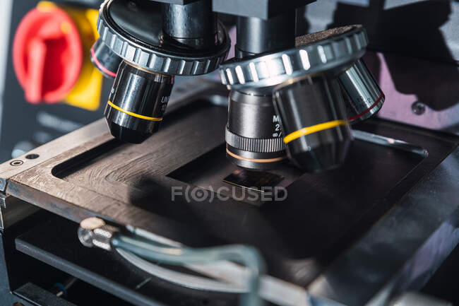 Contemporary professional microscope with powerful lenses placed on table in modern equipped lab — Stock Photo