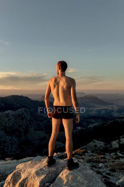 Atrás ver caminante masculino anónimo en calzoncillos negros de pie en la cumbre de la montaña rocosa y admirar los espectaculares paisajes de las tierras altas al atardecer - foto de stock