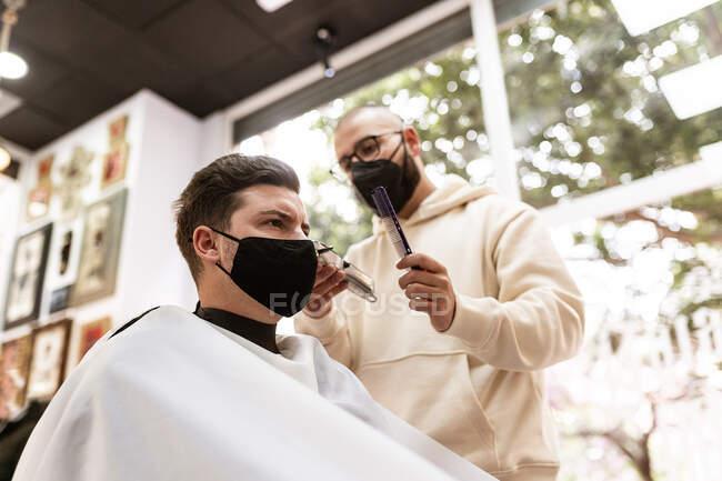 Чоловічий перукар у окулярах робить стрижку для дорослого клієнта у перукарському салоні під час пандемії COVID 19 — стокове фото