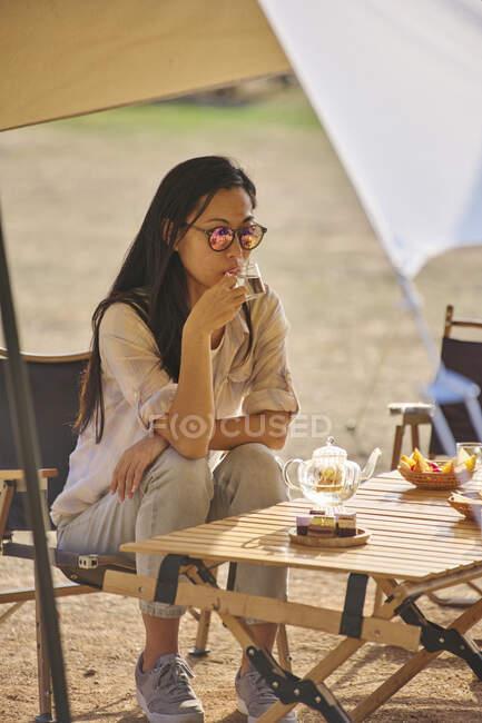 Linda fêmea asiática étnica em óculos de sol sentados à mesa bebendo chá enquanto desfruta de um tempo relaxante na área de acampamento durante as férias — Fotografia de Stock