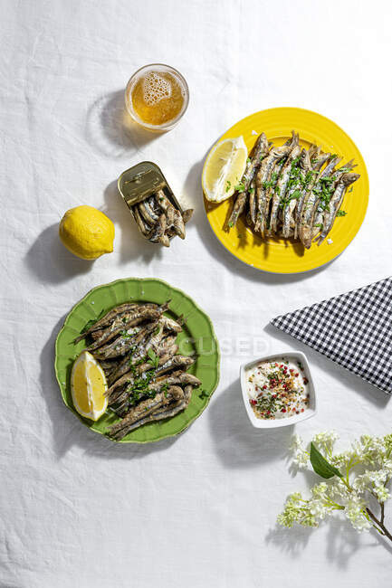 From above of delicious fried anchovies served on plates with lemon and placed on white table with glass of beer - foto de stock