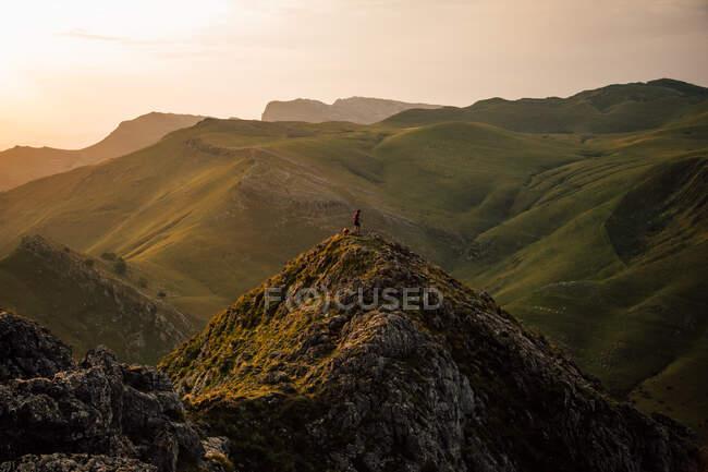 Turista lejano con perro en pico alto de cordillera con pendientes en hierba verde bajo las nubes Txindoki, España - foto de stock