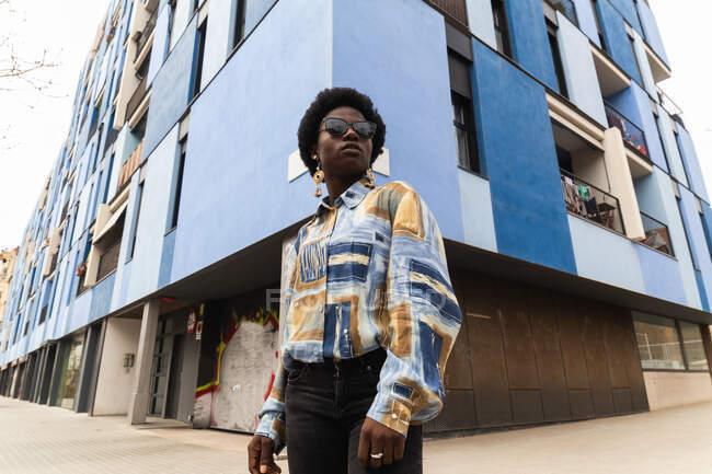 Bajo ángulo de seria joven afroamericana hembra en traje casual y gafas de sol de pie cerca de la esquina del edificio urbano moderno - foto de stock