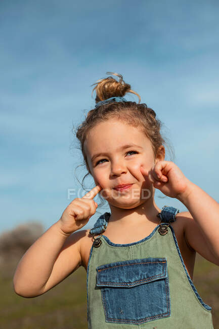 Encantada niña adorable en overoles de pie con los dedos en la cara en el prado y mirando a la cámara - foto de stock
