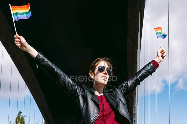 Низький кут змісту самиця з веселкою ЛГБТ прапори в підняті руки стоячи на мосту в місті і дивлячись геть — стокове фото