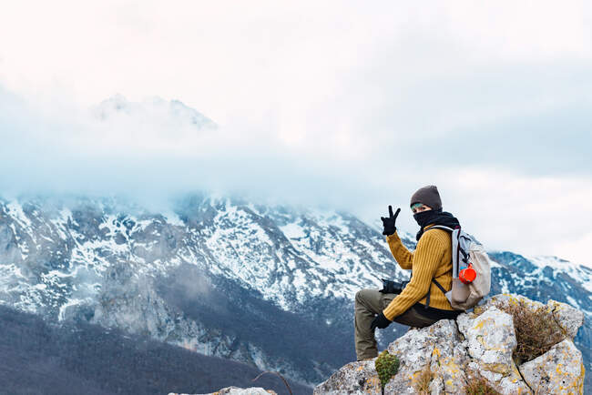Side view of hiker with backpack showing two fingers while sitting on high point of amazing ridge of Peaks of Europe in clouds — Stock Photo