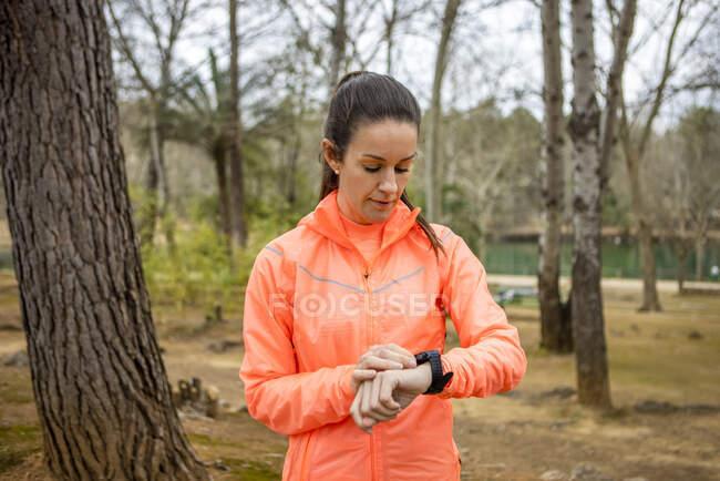 Спортсмен у спортивній манері дивиться серцебиття на зношеному браслеті під час перерви під час тренування в парку на невиразному фоні — стокове фото