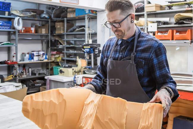 Männlicher Handwerker im Schürzenstand mit Stück Moosgummi für Motorradsitz in der Polsterei — Stockfoto