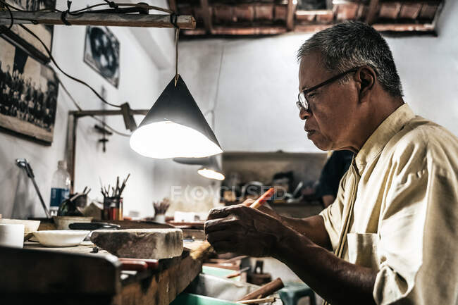Side view of mature ethnic man working at weathered desk in craft workshop — Stock Photo