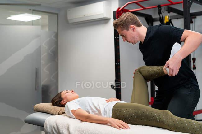Дорослі чоловіки фізіотерапевти торкаються ноги жінки з закритими очима під час обстеження на ліжку в лікарні. — стокове фото