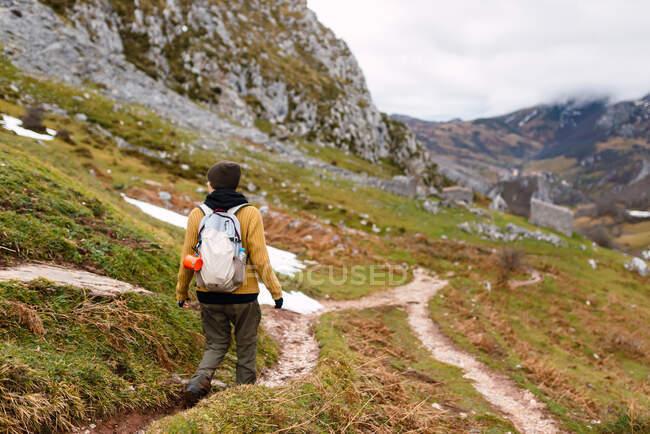 Donna da sogno in abiti caldi che cammina sul pendio della montagna mentre esplora la natura delle vette d'Europa in Spagna — Foto stock
