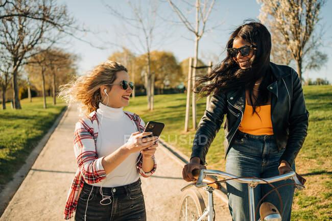 Contenidos multirraciales hembras mejores amigas caminando con bicicleta a lo largo del camino en el parque mientras disfrutan del fin de semana y mirándose — Stock Photo