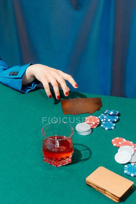 Corte fêmea irreconhecível com cartas e fichas jogando poker enquanto estiver sentado na mesa verde — Fotografia de Stock