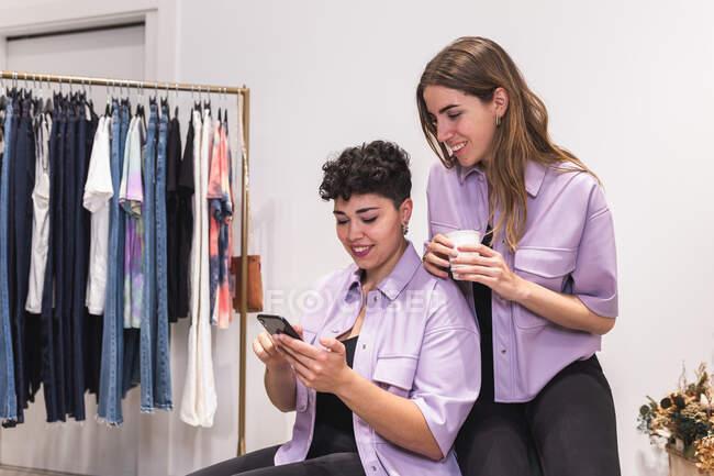 Jovens amigos do sexo feminino positivos na roupa da moda olhando através de informações no telefone na sala de luz com roupas em cabides — Fotografia de Stock