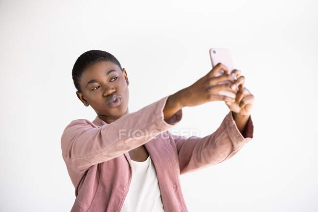 Moda afro-americana feminino enviando beijo ao tomar auto-retrato no celular no fundo branco — Fotografia de Stock