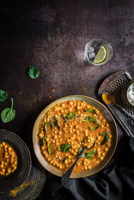Flat lay composition of hearty vegan chickpea curry soup bowl and glass of lime water on black background — Stock Photo