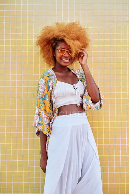 Mulher afro-americana positiva em roupas de verão e óculos de sol em forma de coração na moda em pé no calçadão contra a parede de azulejos amarelos na praia e olhando para a câmera — Fotografia de Stock