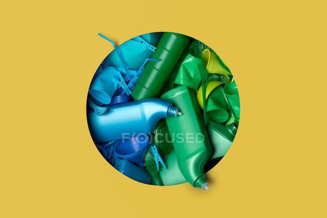 Diversos paquetes de plástico de colores que vienen a través de un agujero en el fondo amarillo - foto de stock