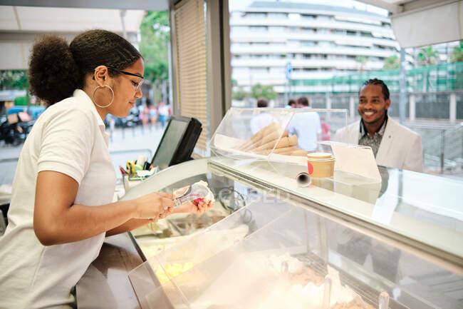 Jovem vendedora feminina negra servindo delicioso gelato para comprador masculino alegre no balcão na cafetaria — Fotografia de Stock