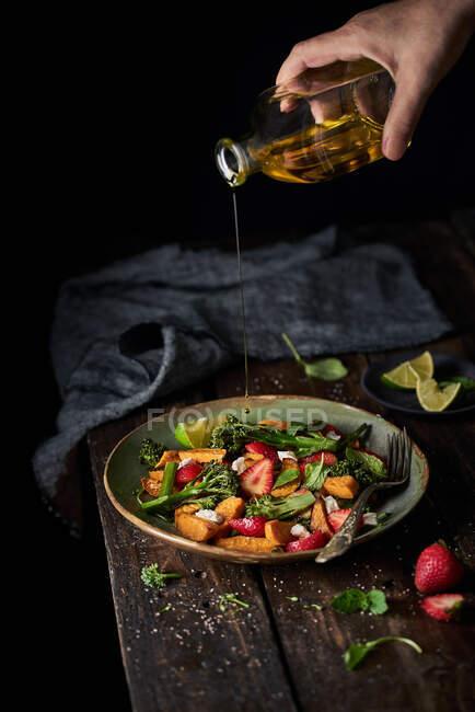 De acima mencionada pessoa sem rosto de colheita derramando o óleo de azeitona da garrafa no verão a salada mista fresca saborosa de frutas e verduras na chapa na mesa de madeira — Fotografia de Stock