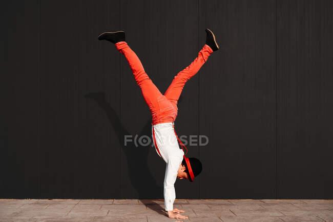 Vista lateral do artista de circo masculino ágil irreconhecível fazendo truque de suporte contra a parede preta — Fotografia de Stock