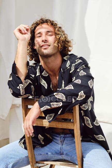 Encantado macho bonito com cabelo encaracolado sentado na cadeira e inclinado na mão enquanto olha para a câmera no fundo de cortinas brancas — Fotografia de Stock
