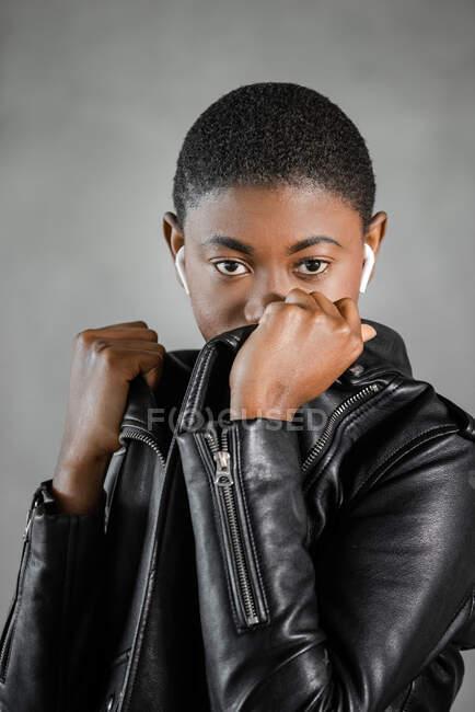 Jovem mulher afro-americana na moda com cabelo curto cobrindo a boca com jaqueta de couro enquanto olha para a câmera no fundo borrado — Fotografia de Stock