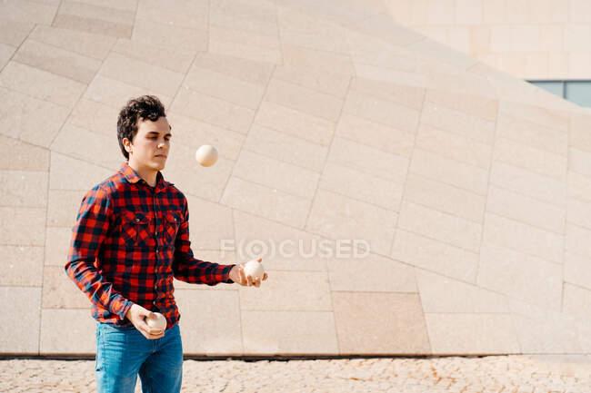 Habilidade jovem macho em camisa quadriculada realizando truque com bolas de malabarismo, enquanto em pé contra a estrutura de concreto contemporâneo na rua urbana — Fotografia de Stock