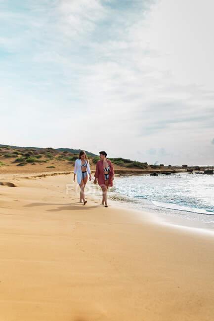 Corpo inteiro de descalço de namoradas em trajes de banho passeando ao longo da costa lavada por ondas espumosas durante as férias de verão — Fotografia de Stock