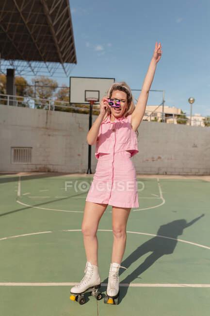 Comprimento total feminino ajuste alegre em rosa sundress patinação em rolos com braço levantado e tirar fotos na câmera de fotos instantâneas no chão de esportes ensolarado — Fotografia de Stock