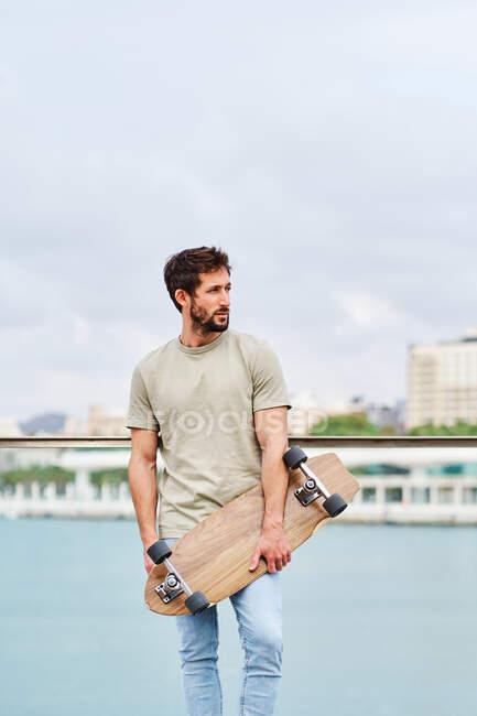 Corpo inteiro jovem macho sem emoção em roupas casuais segurando skate e olhando para longe enquanto estava no calçadão perto do lago da cidade — Fotografia de Stock