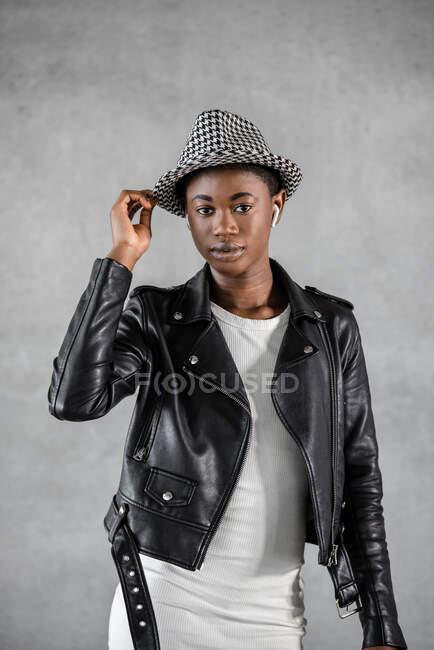 Jovem afro-americana em fone de ouvido e jaqueta de couro tocando chapéu elegante enquanto olha para a câmera — Fotografia de Stock