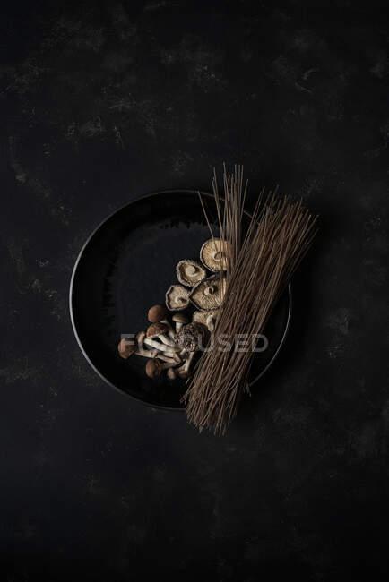 Vista superior de cogumelos frescos e macarrão marrom duro na panela para cozinhar prato coreano Japchae — Fotografia de Stock