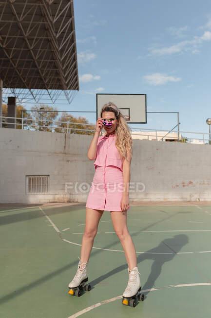 Comprimento total feminino ajuste alegre em rosa sundress patinação em rolos tirando fotos na câmera de foto instantânea no chão de esportes ensolarado olhando para a câmera — Fotografia de Stock